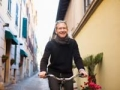 Man bicycles along a small town corrador, 6 Ways to Stay Healthy on Vacation