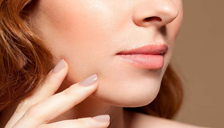 Mujer tocándose la cara - Preguntas al cirujano plástico