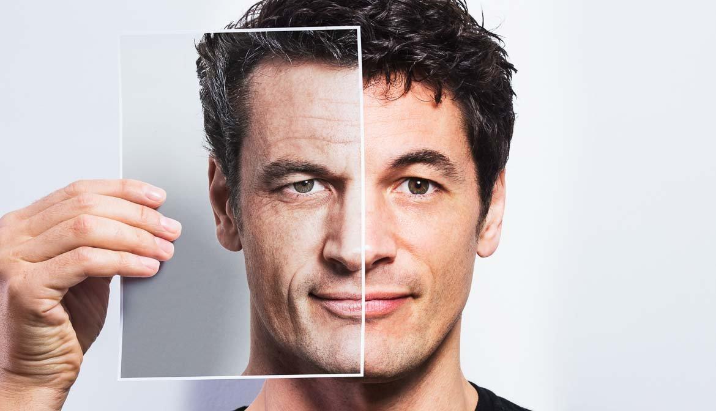 Hombre sosteniendo una foto de si mismo, pero mayor - Preguntas al cirujano plástico