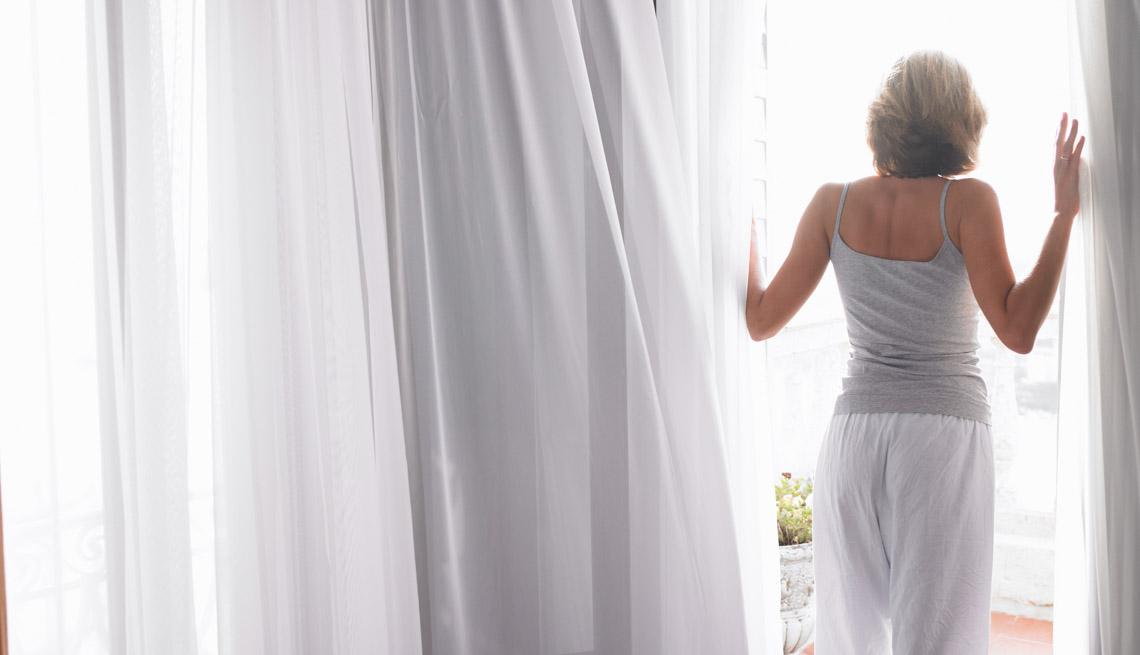 Mujer abriendo sus cortinas - Mañanas mas saludables