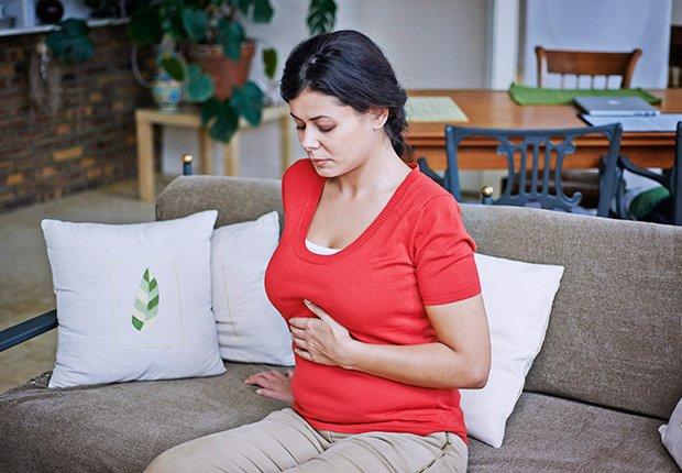 Mujer con su mano en el abdomen en señal de malestar