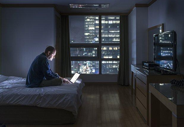 Hombre sentado en su cama con el computador a media noche