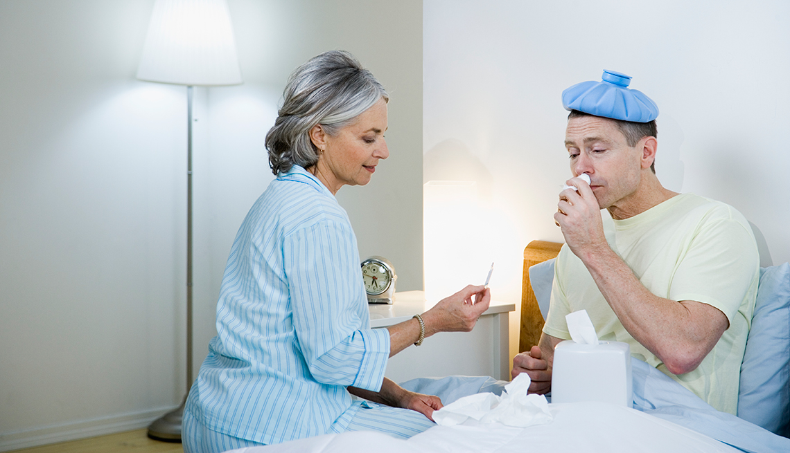 Woman taking temperature of sick man in bed
