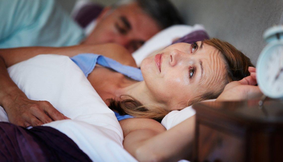 Mujer acostada sin poder dormirse