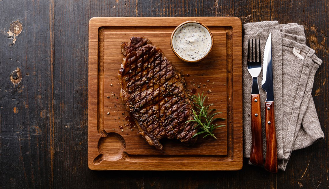 Grilled Steak Striploin and Pepper sauce on cutting board on dark wooden background