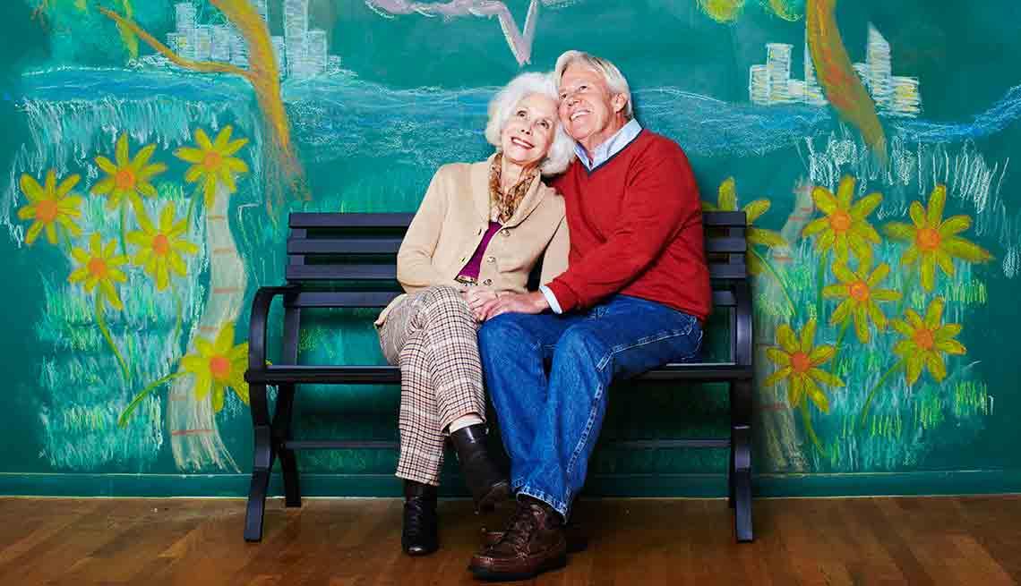 Pareja de adultos mayores abrazados mientras sonríen.