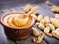 Recipiente con mantequilla de maní y frutos de mani al lado - La mantequilla de maní te puede hacer más saludable