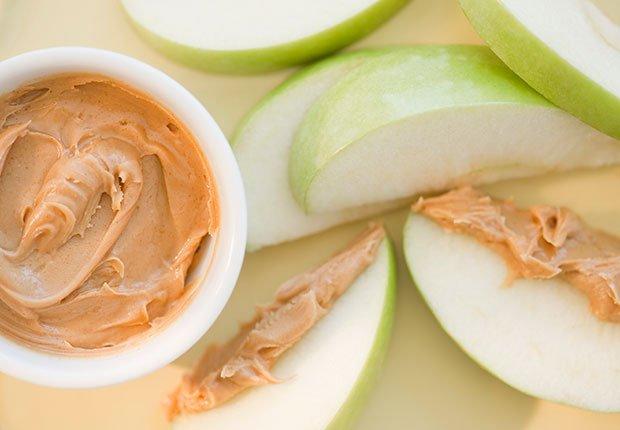 Recipiente con mantequilla de maní y pedazos de manzana al lado - La mantequilla de maní te puede hacer más saludable