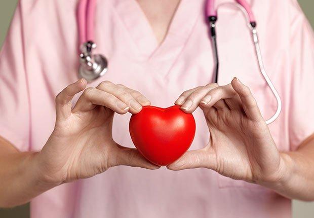 Mujer con uniforme de enfermera sosteniendo un corazón rojo de espuma - La mantequilla de maní te puede hacer más saludable