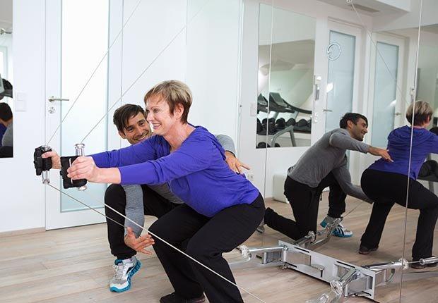 Mujer haciendo ejercicios de sentadilla ayudada por un entrenador personal - La mantequilla de maní te puede hacer más saludable