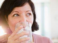 Mujer tomando agua con hielo en un vaso de vidrio - Enfermedades y transtornos que puedes evitar o aliviar tomando agua