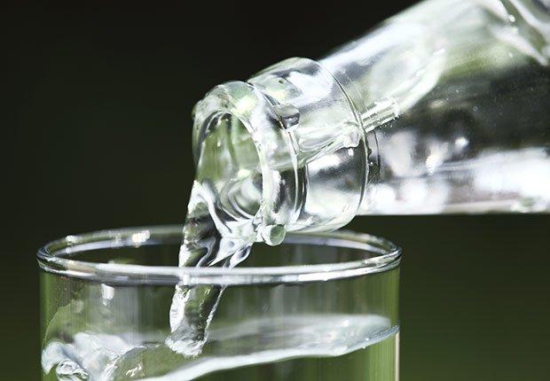 Vaso de vidrio en el que se coloca agua de una botella de vidrio - Enfermedades y transtornos que puedes evitar o aliviar tomando agua
