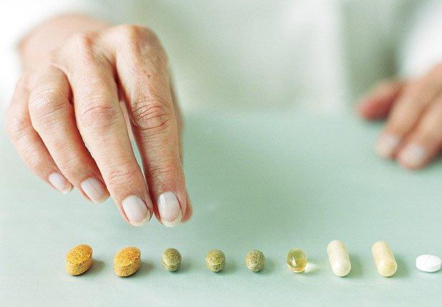 Manos de una mujer agarrando unas pastillas - Hábitos que te ayudan a dormir mejor