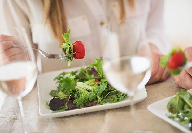 Mujer comiendo una ensalada y copas con agua - Enfermedades y transtornos que puedes evitar o aliviar tomando agua