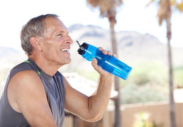 Hombre mayor en un gimnasio tomando agua de una botella de plástico - Enfermedades y transtornos que puedes evitar o aliviar tomando agua