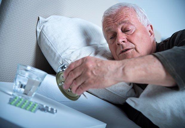 Hombre mayor acostado en una cama y chequeando un reloj de cuerda - Enfermedades y transtornos que puedes evitar o aliviar tomando agua