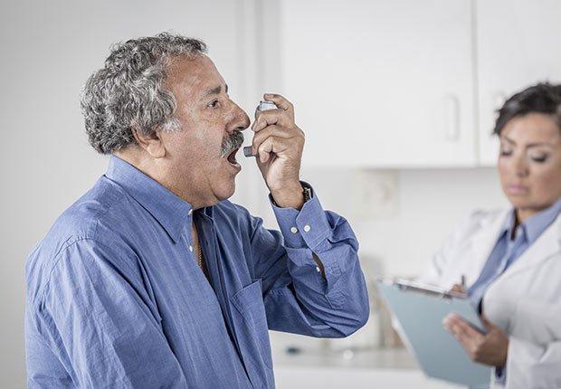 Hombre mayor en un consultorio usando un inhalador para el asma - Enfermedades y transtornos que puedes evitar o aliviar tomando agua