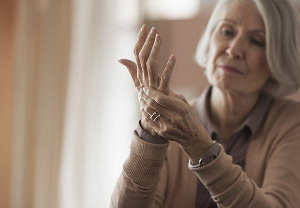 Mujer mayor tocándose una mano - Enfermedades y transtornos que puedes evitar o aliviar tomando agua