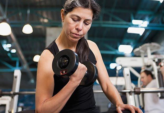 Mujer levantando pesas en un gimnasio - Hábitos que te ayudan a dormir mejor