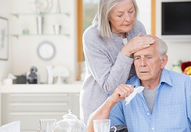 Mujer mayor tocando la frente de un hombre mayor sentado frente a una mesa - Enfermedades y transtornos que puedes evitar o aliviar tomando agua