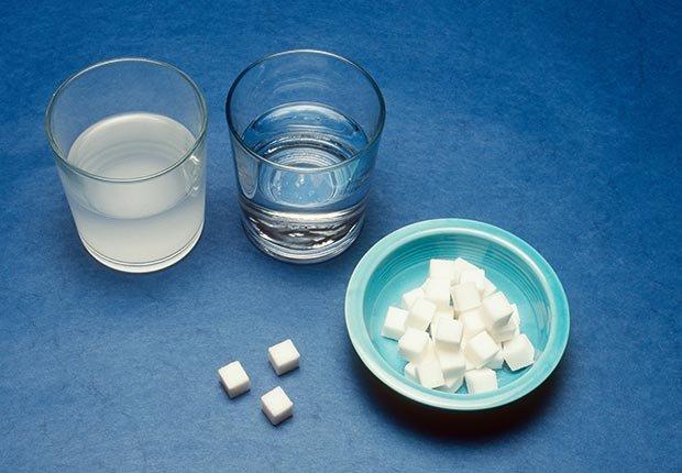Dos vasos de agua, uno de ellos con azúzcar y un plato con cubos de azúcar - Enfermedades y transtornos que puedes evitar o aliviar tomando agua