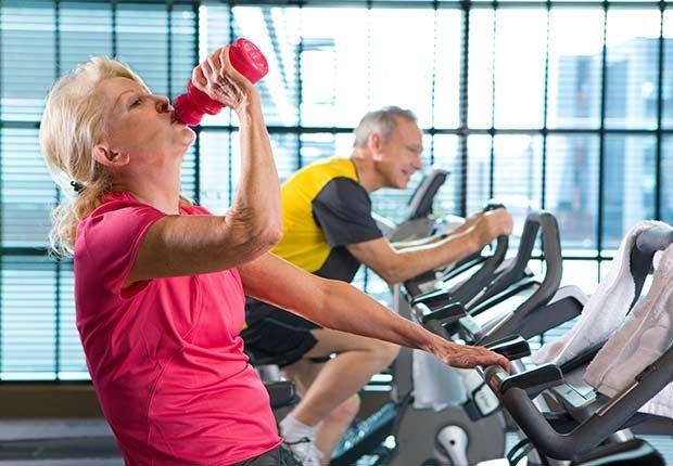 Mujer mayor en un gimnasio sentada en una bicicleta estática y tomando agua de una botella de plástico - Enfermedades y transtornos que puedes evitar o aliviar tomando agua