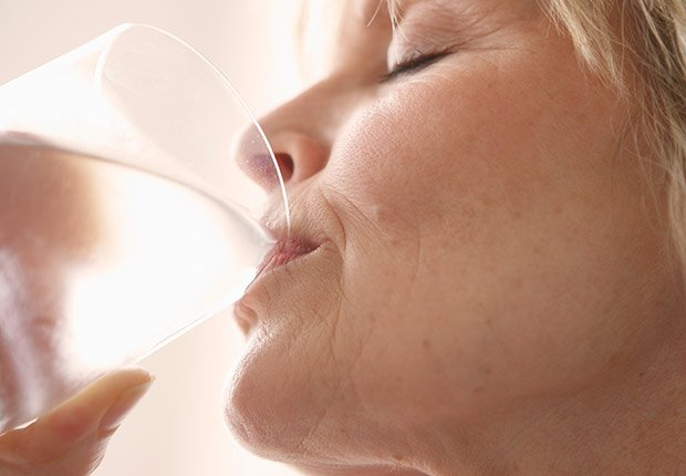 Mujer con los ojos cerrados tomando agua de un vaso de vidrio - Enfermedades y transtornos que puedes evitar o aliviar tomando agua