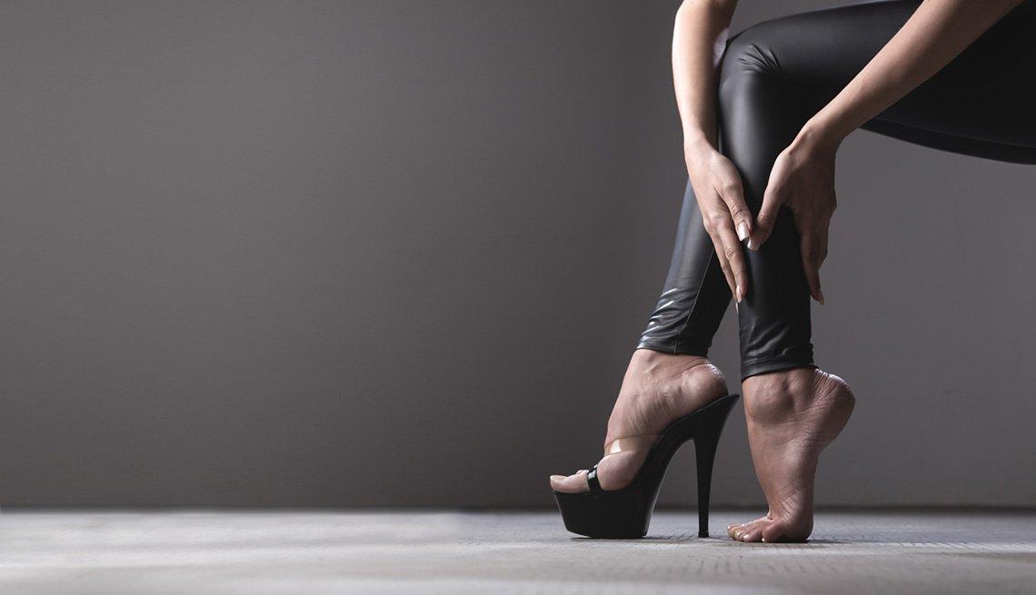 Mujer masajeando su pierna luego de usar tacones muy altos