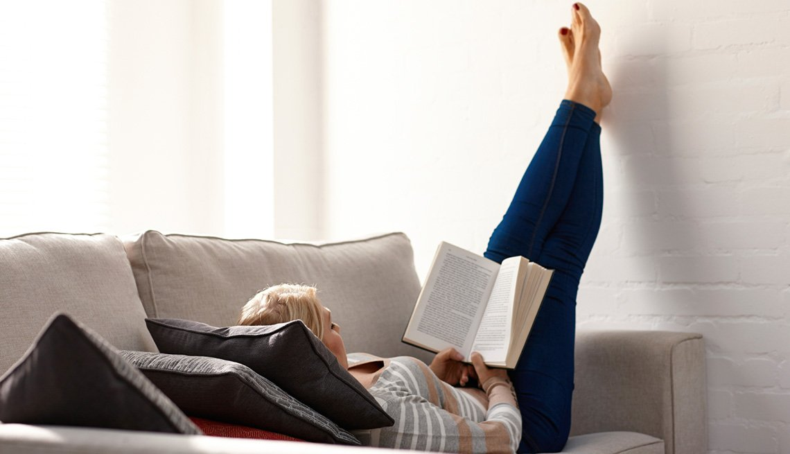 Mujer leyendo muy relajada en un sofá