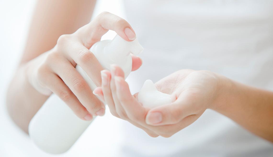 Mujer poniéndose crema limpiadora facial en su mano