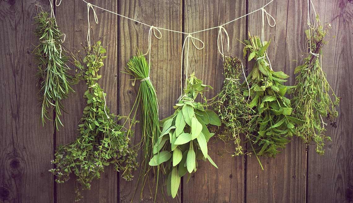 Distintas hierbas culinarias colgando de una cuerda