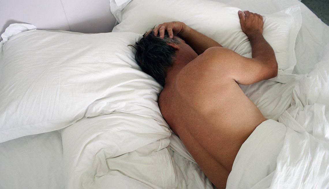 Hombre acostado de lado en su cama