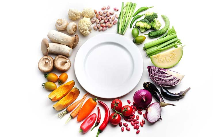 Vegetales y frutas rodeando un plato vacío al centro - Frutas y vegetales que podrían causar alergias