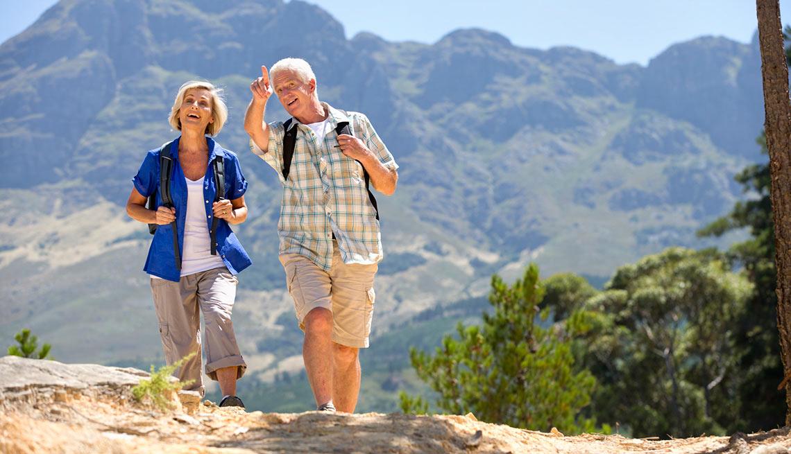Pareja de adultos mayores haciendo una caminata por un parque