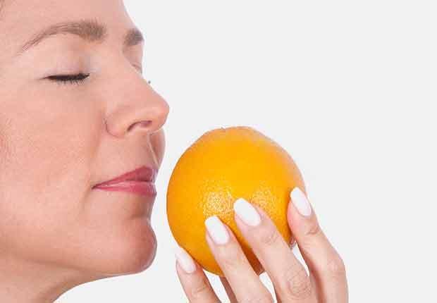 Mujer oliendo una naranja
