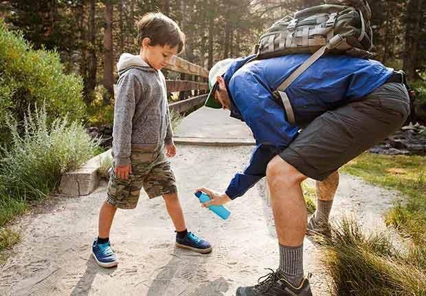 Papá rociando a su hijo con aerosol contra mosquitos