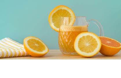 Naranjas cortadas a la mitad y jugo de naranja servido - Efecto del azúcar en el cuerpo