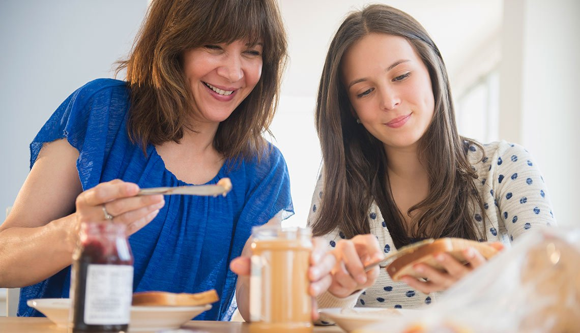Madre e hija preparando emparedados de jalea y mantequilla de maní