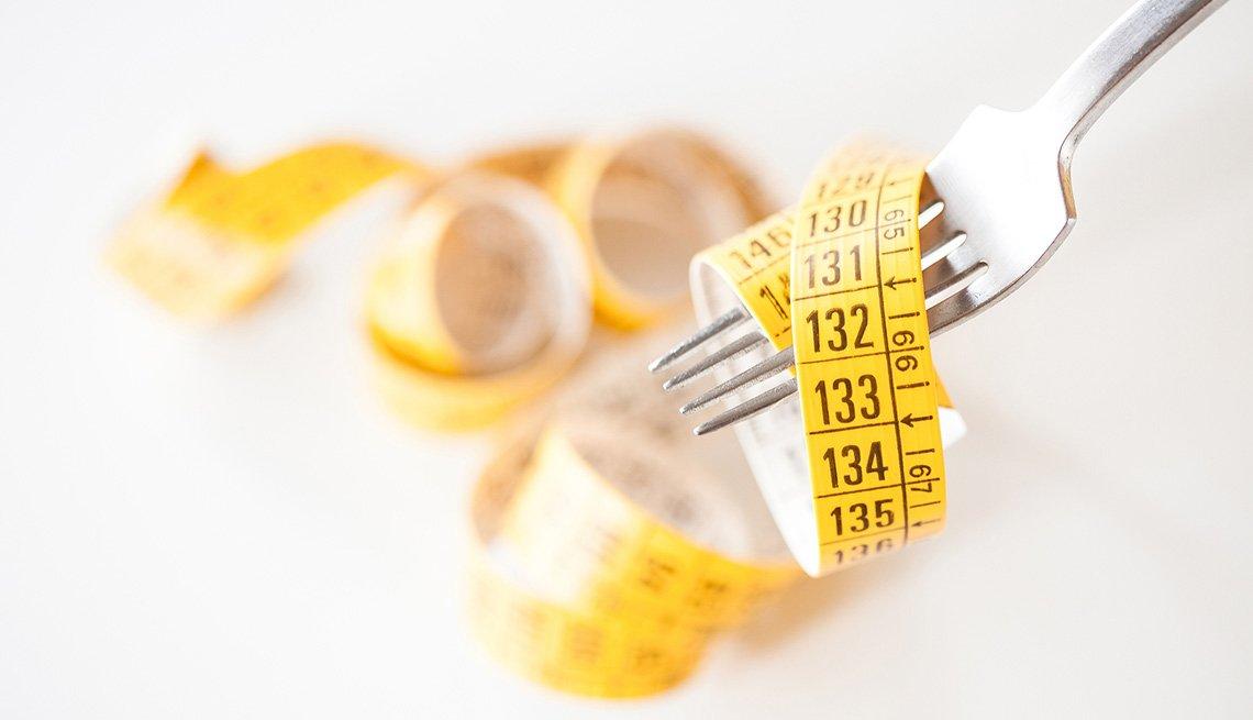 Tenedor y una cinta de medir - Perder peso es bueno para combatir la inflamación