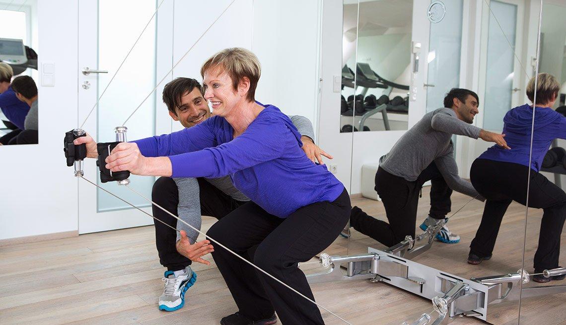 Mujer madura haciendo ejercicios junto a un entrenador personal