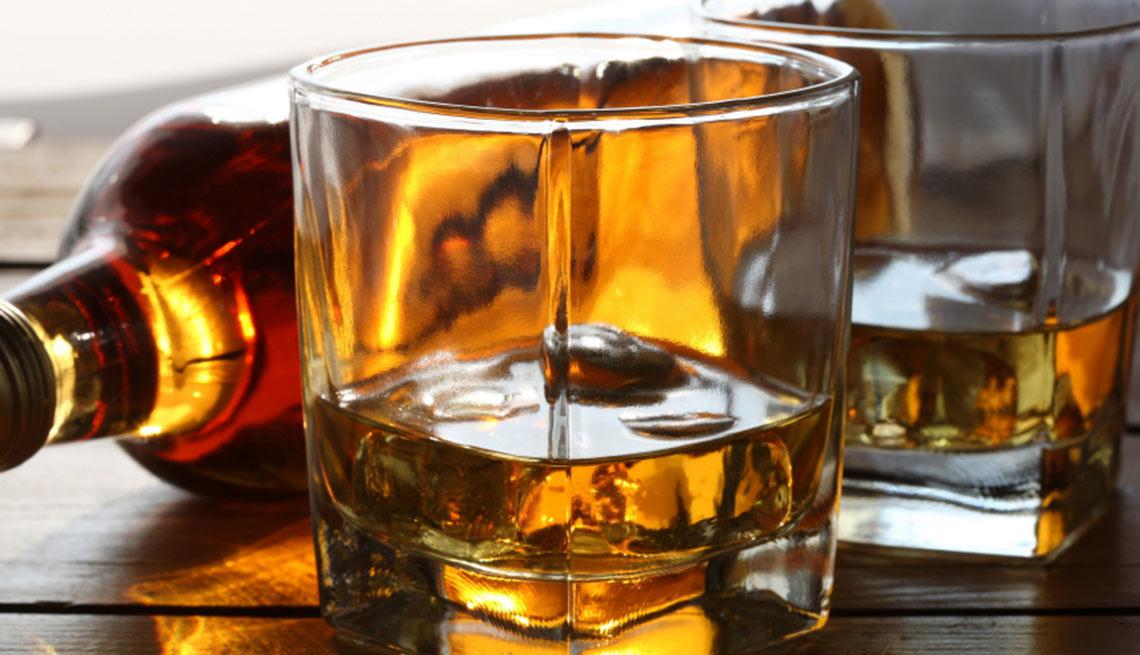 Botella de whiskey y vasos servidos