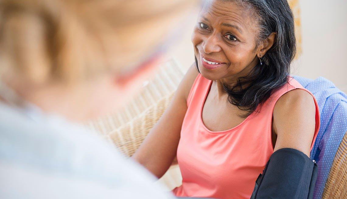 Personal médico tomándole la presión a una mujer