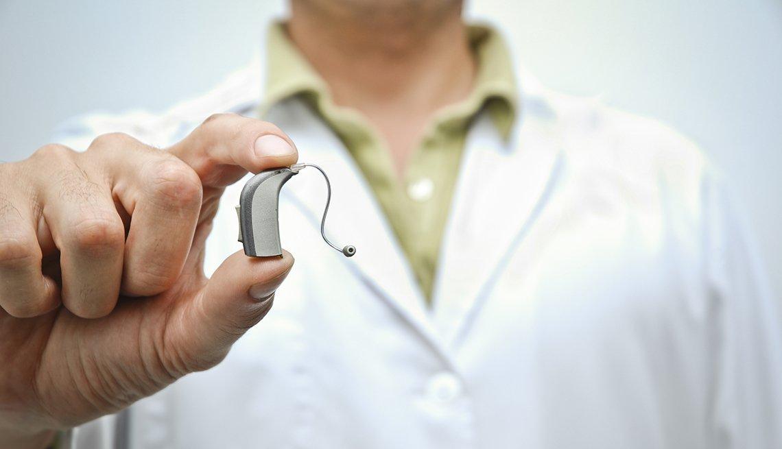 Personal médico sosteniendo un audífono