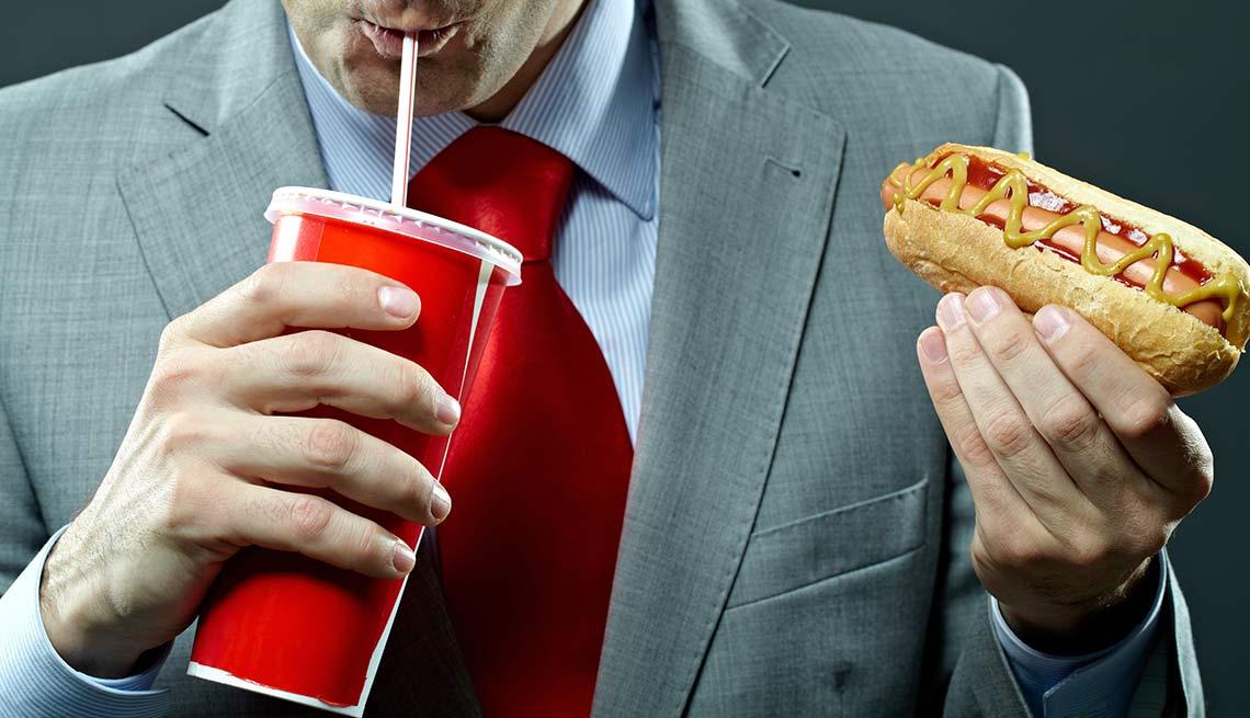 Hombre tomando soda y comiendo un hot dog