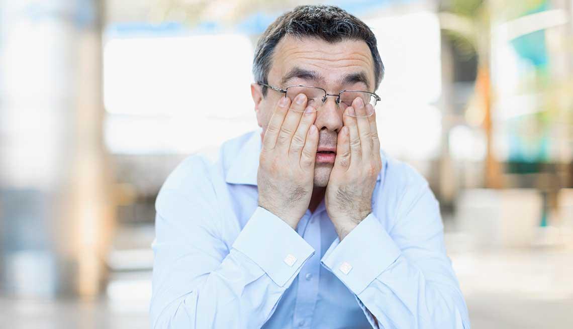 Hombre rascando sus ojos en señal de agotamiento