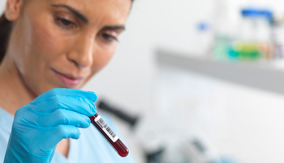 Empleada de un laboratorio observando un tubo de ensayo con una muestra de sangre