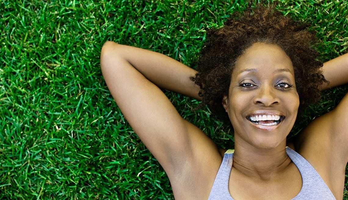 Mujer sonreida acostada en la grama