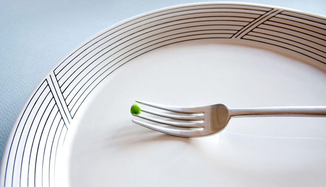 Plato y un tenedor pinchando un guisante