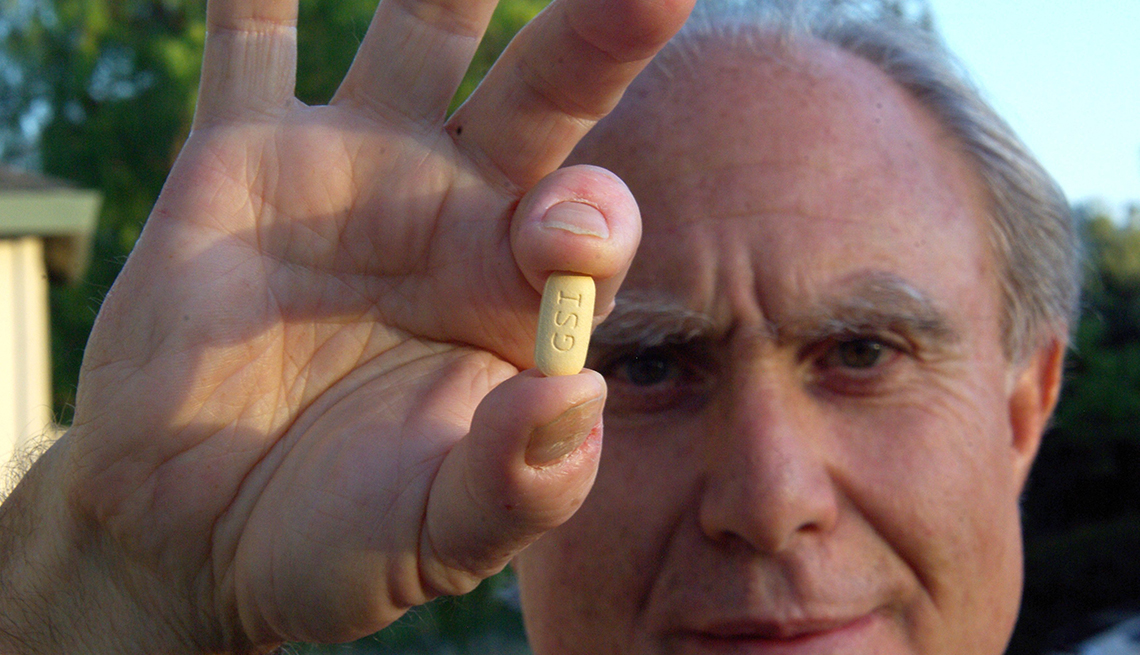Hombre sosteniendo una píldora en su mano