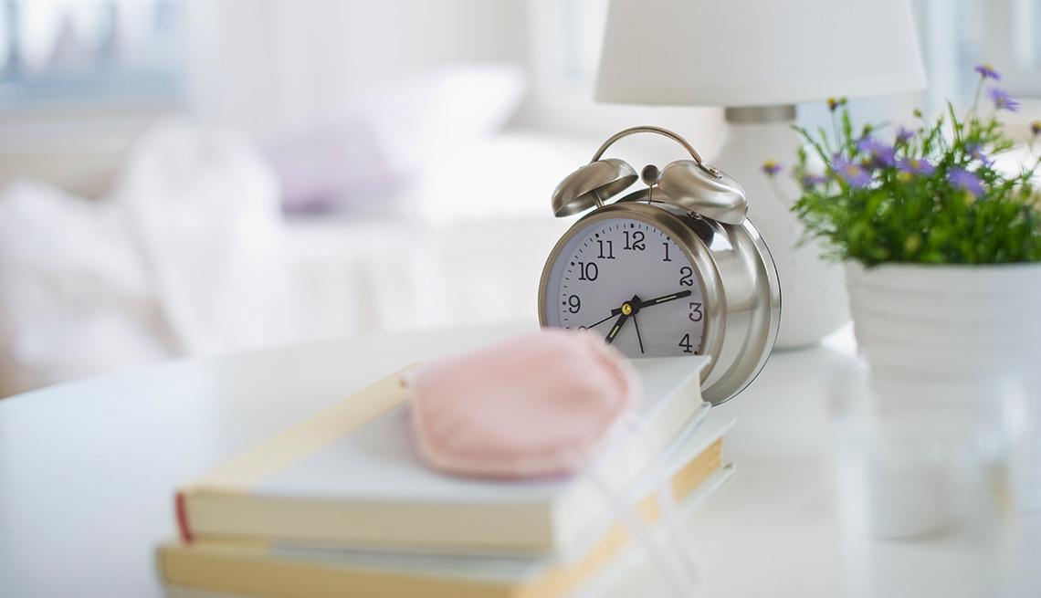 Mesa de cama con reloj despertador, libros, lámpara y una planta